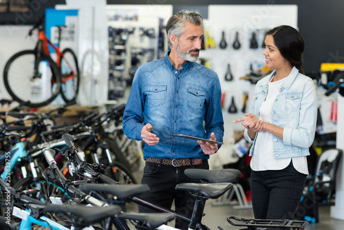 salesman and female client looking at bicycles