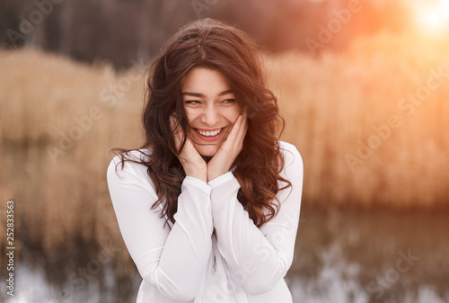 Fotografie, Obraz  Beautiful laughing brunette with hands on cheeks