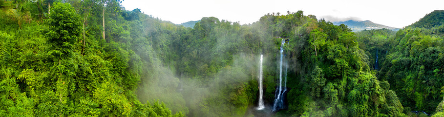 FototapetaAerial over Sekumpul waterfall surrounded by dense rainforest and mountains shrouded in mist at sunrise, Bali, Indonesia panoramic