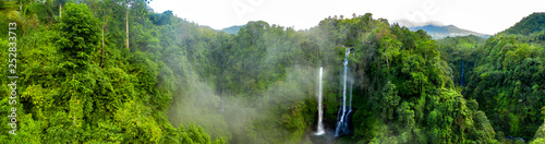 Aerial over Sekumpul waterfall surrounded by dense rainforest and mountains shrouded in mist at sunrise, Bali, Indonesia panoramic - fototapety na wymiar