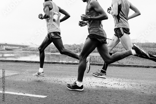 Fotografía group runners leaders run along embankment of river black-and-white image