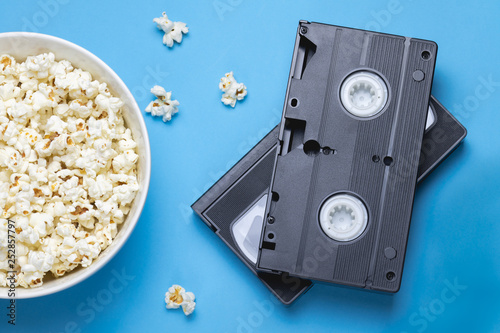 Two black VHS tapes, bowl of popcorn and scattered popcorns on a blue background Billede på lærred