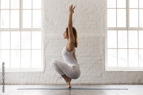 Fotografia Sporty woman standing in Utkatasana pose, Squat, Chair exercise