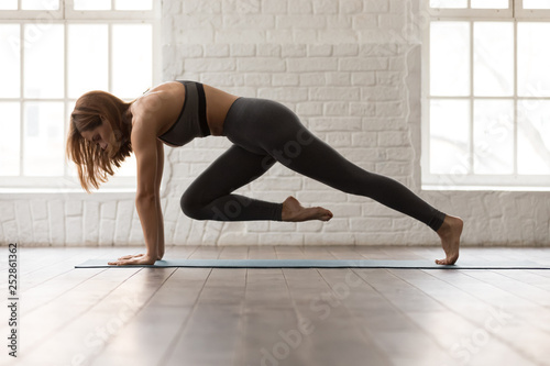 Cuadros en Lienzo Woman practicing yoga, doing Knee to Forehead exercise, Plank pose