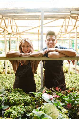 Happy gardeners posing in the nature greenhouse garden.