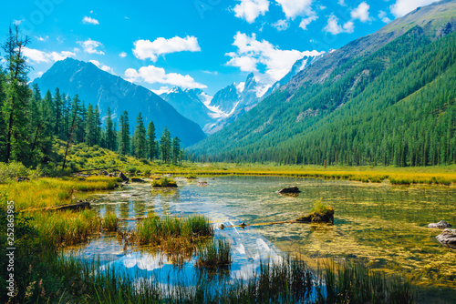 Beautiful glacier reflected in mountain pure water with plants on bottom. Wonderful lake with snowy rocks reflection. White clouds on snowy mountains under blue sky. Amazing summer highland landscape.