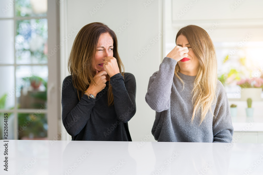 Fototapety, obrazy: Beautiful family of mother and daughter together at home smelling something stinky and disgusting, intolerable smell, holding breath with fingers on nose. Bad smells concept.