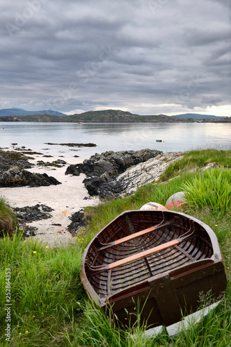 Canvas-taulu Sand beach and rocky shore of Isle of Iona with beached boat and view of Fionnph