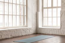 Yoga Mat On Wooden Floor In Empty Room In Yoga Studio