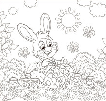 Little Bunny Coloring A Big Easter Egg On Grass Among Flowers On Its Front Lawn Near A Small Hut With Thatched Roof On A Sunny Spring Day, Black And White Vector Illustration In A Cartoon Style