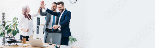 colleagues at table with laptop smiling and highing five in office