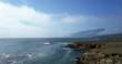 Gorgeous mountain coast line beside calm ocean - aerial tracking shot