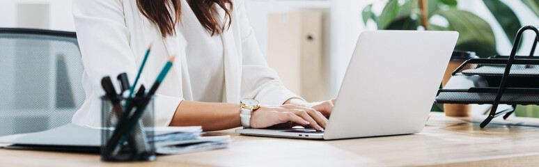 cropped view of businesswoman sitting at table with laptop and typing in office