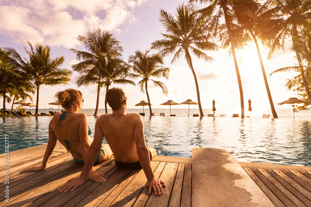 Fototapeta Couple enjoying beach vacation holidays at tropical resort with swimming pool and coconut palm trees near the coast with beautiful landscape at sunset, honeymoon destination