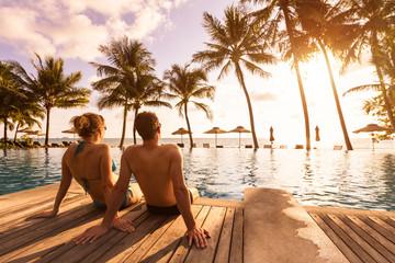 Par koji uživa u odmoru na plaži u tropskom ljetovalištu s bazenom i kokosovim palmama u blizini obale s prekrasnim krajolikom u zalasku sunca, odredište za medeni mjesec