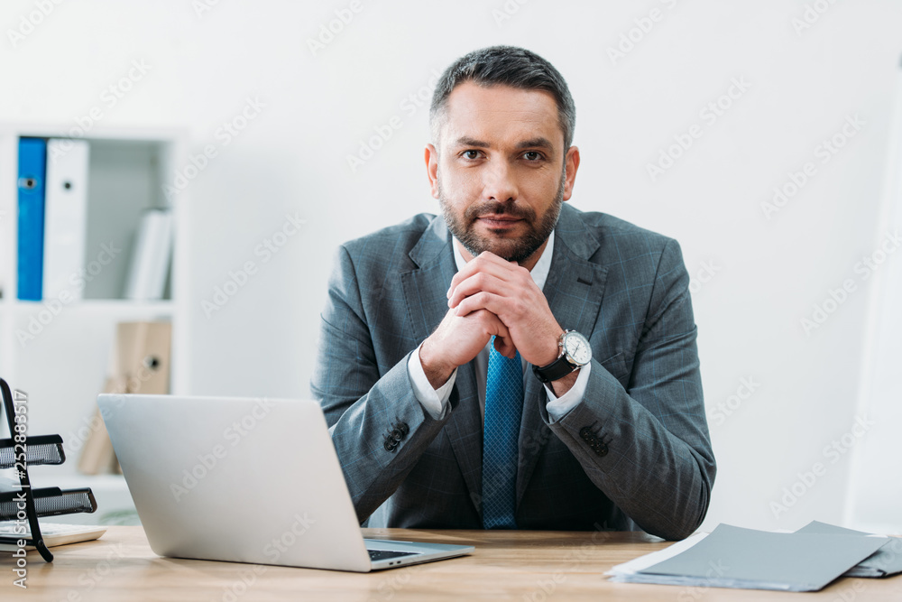Fototapeta handsome businessman sitting at table with laptop and looking at camera in office