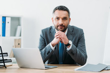 Handsome Businessman Sitting At Table With Laptop And Looking At Camera In Office