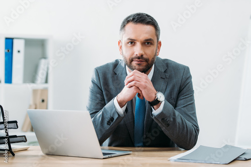 Fototapeta handsome businessman sitting at table with laptop and looking at camera in office obraz