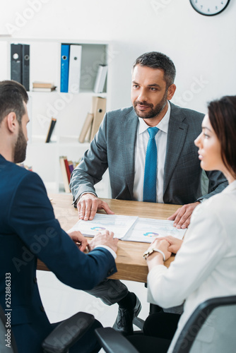 selective focus of advisor and investors in suits talking about document at worp Canvas Print