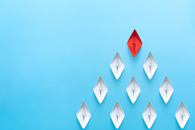 Leadership Concept. Red Leader Paper Ship Leading Among White On Blue Background. Copy Space