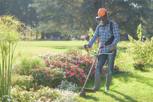 Man Mowing The Grass With Portable Machine In The Garden