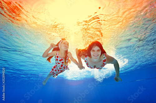 Photographie  Happy mother and daughter swim under the water holding hands against the bright orange sunset in the same dresses