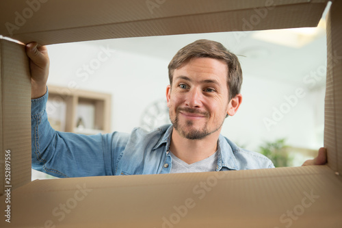 Fotografiet  smiling young man looking into cardboard box