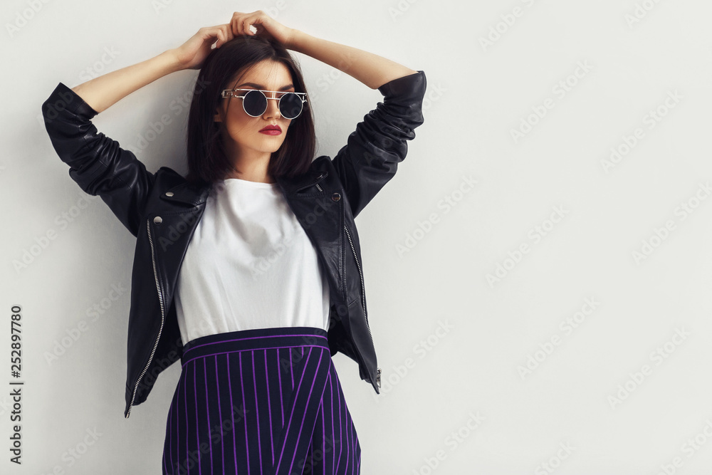 Fototapeta Young beautiful woman in a black jacket and sunglasses