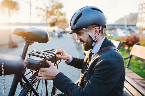 Hipster businessman commuter setting up electric bicycle in city. Wallpaper Mural