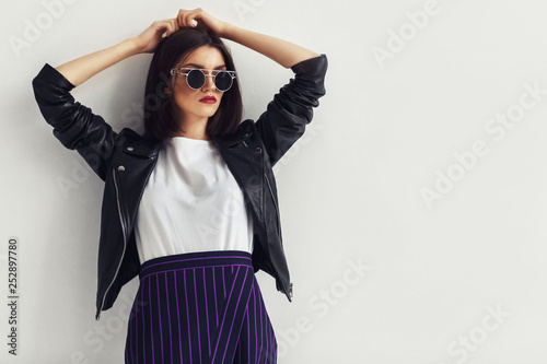 Fotografía  Young beautiful woman in a black jacket and sunglasses