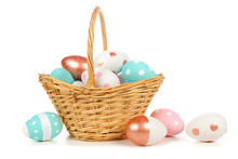 Easter Basket Filled With Colorful Hand Painted Pink, Blue, White And Rose Gold Easter Eggs Isolated On A White Background