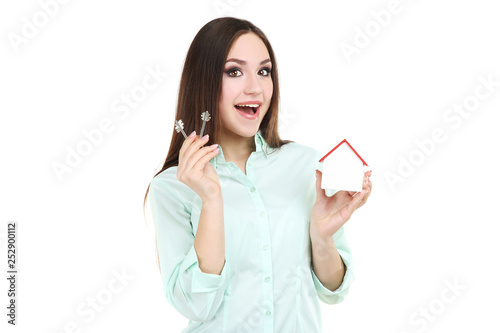 Fotografía  Young woman showing keys and wooden house on white background