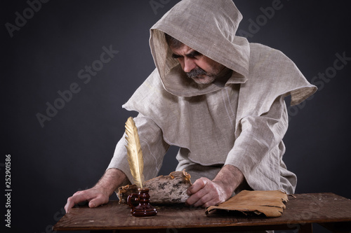 Fotografia  A monk alchemist is engaged in science, studying ancient manuscripts on birch ba