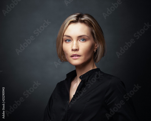 Fototapeta Beautiful middle-aged woman on a gray background in a black blouse. obraz
