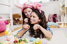 Mother And Her Cute Little Daughter Playing In Children's Room While Preparing Easter Decoration.
