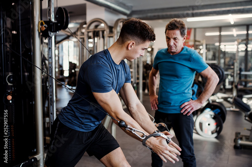 Fotografia A senior man with a young trainer doing strength workout exercise in gym