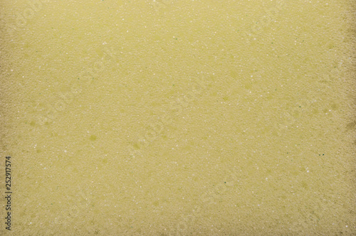 Fotografie, Obraz  The texture of the porous surface of the sponge is yellow.
