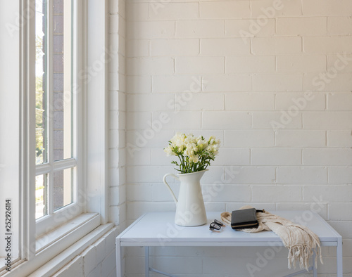 White freesias in jug on table with scarf, purse and glasses against painted brick wall next to window with copy space Fototapete
