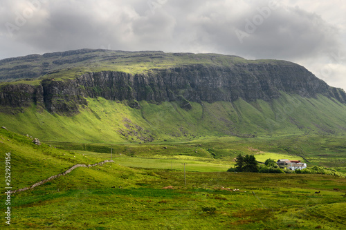 Poster Cote Farm at Balmeanach with cliffs of Creag a Ghaill green slopes and on Loch Na Keal Isle of Mull Scottish Highlands Scotland UK