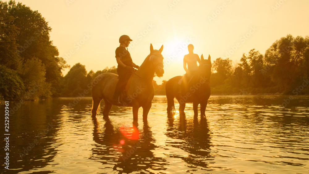 Fototapety, obrazy: SILHOUETTE: Horseback riders stop their horses while riding them along a stream.