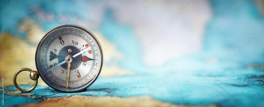 Fototapeta Magnetic old compass on world map.Travel, geography, navigation, tourism and exploration concept wide background. Macro photo. Very shallow focus.