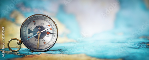 Poster Northern Europe Magnetic old compass on world map.Travel, geography, navigation, tourism and exploration concept wide background. Macro photo. Very shallow focus.