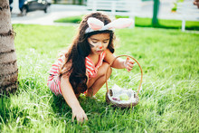 Cute Little Girl With Bunny Ears And Basket Of Easter Eggs In The Garden. Easter Egg Hunt