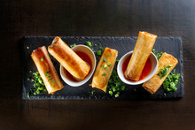 Fried Spring Rolls On Black Slate Decorated With Greens.