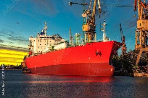 Fotografía Cargo ship in port at sunset time.