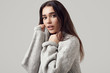 Beautiful brunette woman in sweater posing in studio
