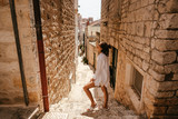Fototapeta Na drzwi - Young girl walking through ancient narrow streets on a beautiful summer day