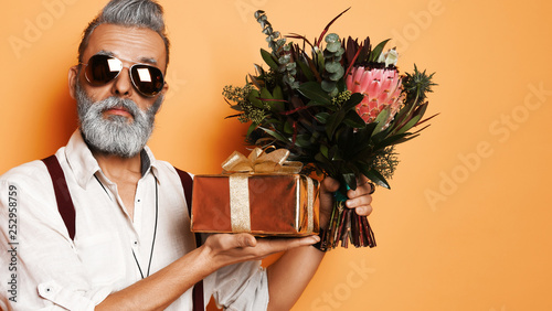 Fotografiet  Brutal senior bearded old man in aviator sunglasses with a bunch of flowers and