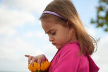 Portrait Of Little Girl Watching Some Sunflowers