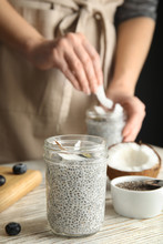 Jar Of Tasty Chia Seed Pudding With Coconut On Table Against Blurred Background